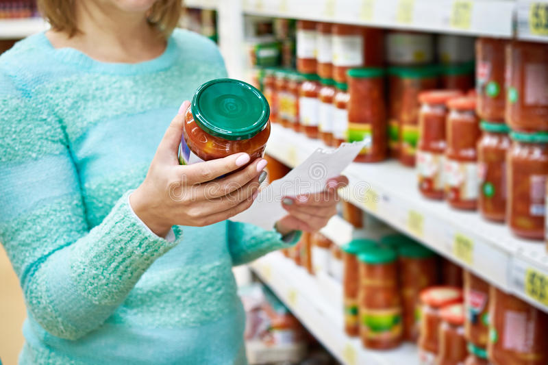 Woman chooses lecho tomato at grocery store. Woman chooses lecho tomato at the grocery store royalty free stock image
