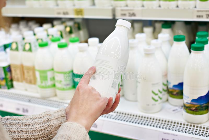Woman chooses milk and dairy products at store royalty free stock photos