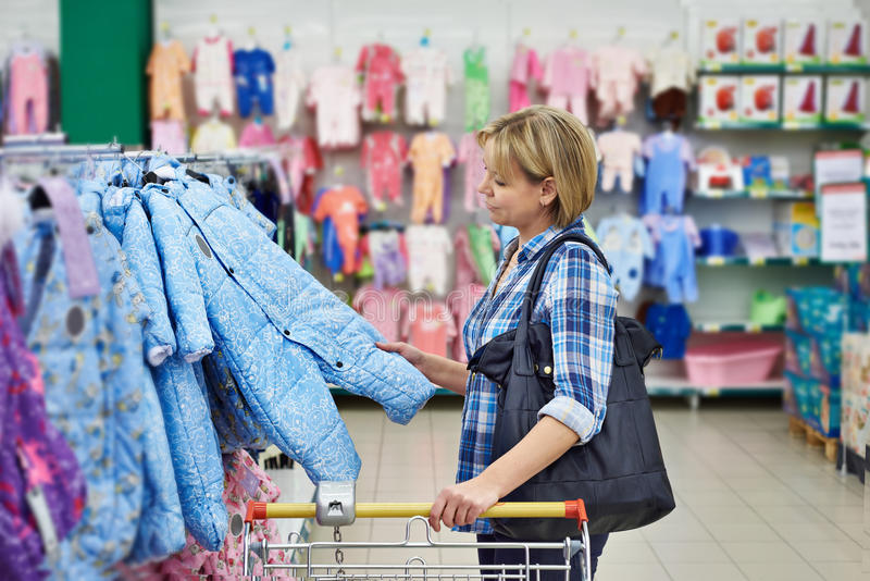 Woman chooses rompers in store stock photo