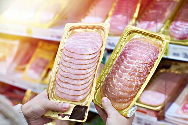 Woman chooses slice of ham at store. Woman chooses a slice of ham and meat in vacuum package at the grocery store stock photography