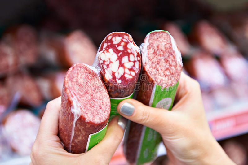 Woman chooses smoked sausage in store. Woman chooses smoked sausage in the store royalty free stock image