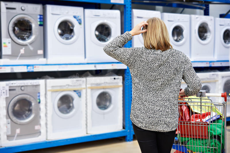 Woman chooses washing machine in shop of home appliances stock photos