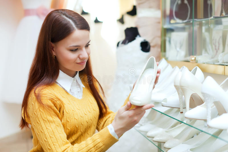 Woman chooses white shoes. At fashionable shop royalty free stock photography