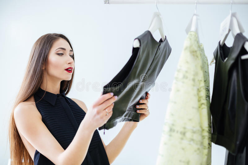 Woman choosing cloth in store. Young woman choosing cloth in store royalty free stock photography