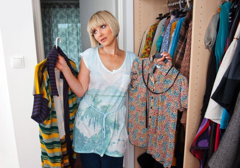 Woman choosing clothes stock photos