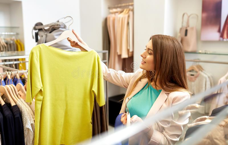 Woman choosing clothes at clothing store. Shopping, fashion, sale and people concept - young woman choosing clothes in mall or clothing store royalty free stock image