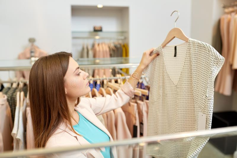 Woman choosing clothes at clothing store. Shopping, fashion, sale and people concept - young woman choosing shirt in mall or clothing store stock photos