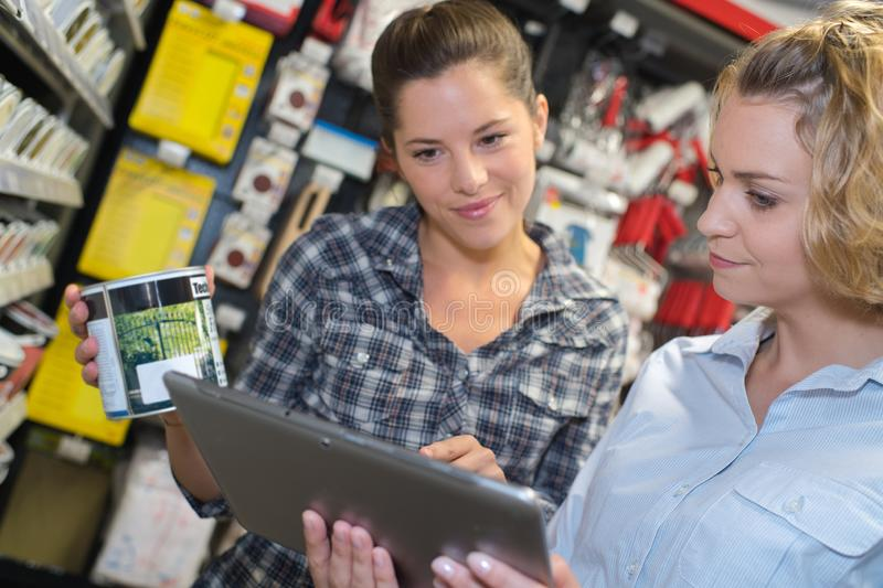 Woman choosing color paint during hardware shopping in home improvement. Warehouse stock images