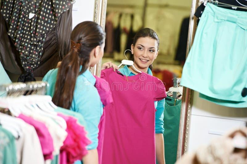 Woman shopping clothng. Woman choosing dress during shopping at garments apparel clothing shop royalty free stock image