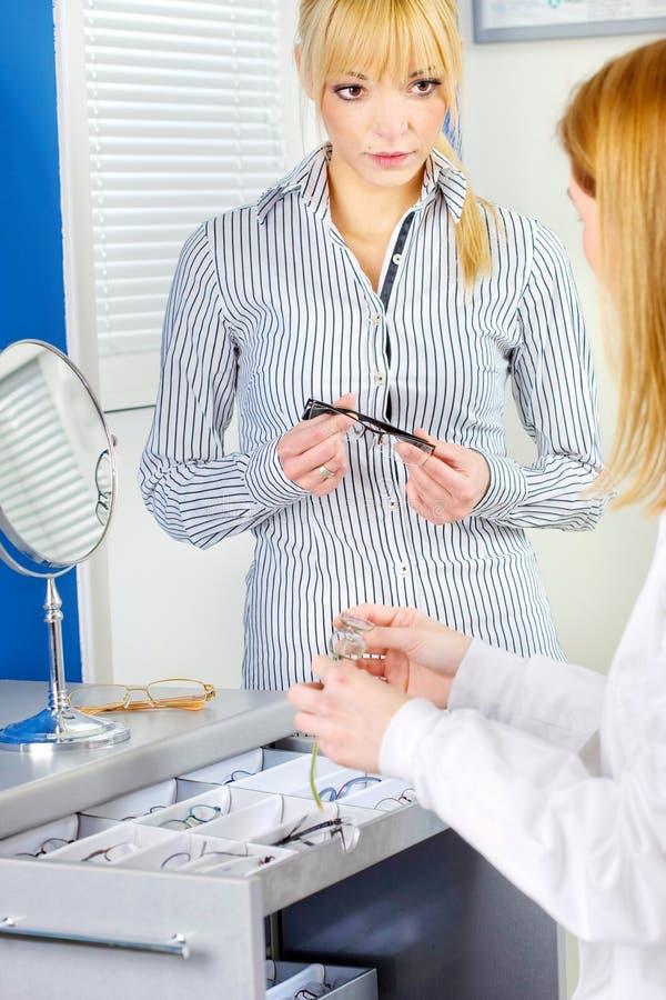 Download Woman Choosing Eyeglasses At Optometrists Stock Photo - Image: 22610798