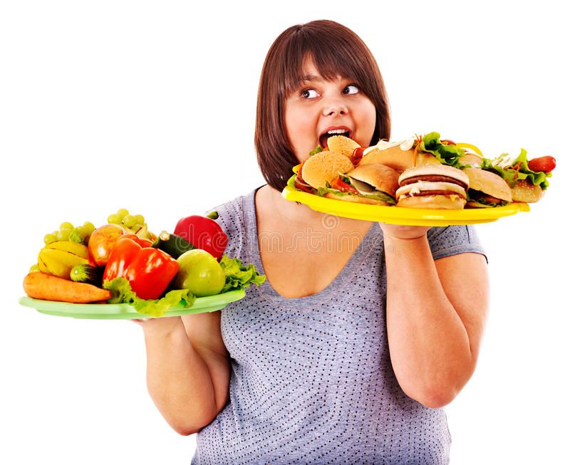 Woman choosing between fruit and hamburger. Isolated royalty free stock image