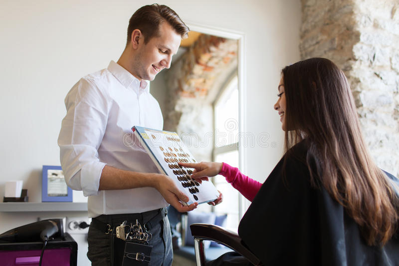Woman choosing hair color from palette at salon stock photo