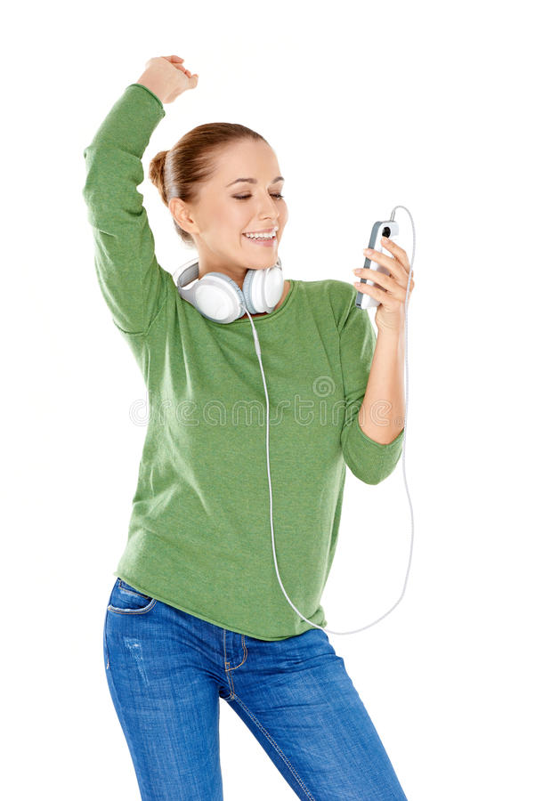 Woman choosing her downloaded music. Beautiful young woman with headphones slung around her neck smiling at her choice of downloaded music on her storage device royalty free stock image