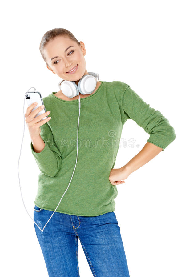 Woman choosing her downloaded music. Beautiful young woman with headphones slung around her neck smiling at her choice of downloaded music on her storage device royalty free stock images