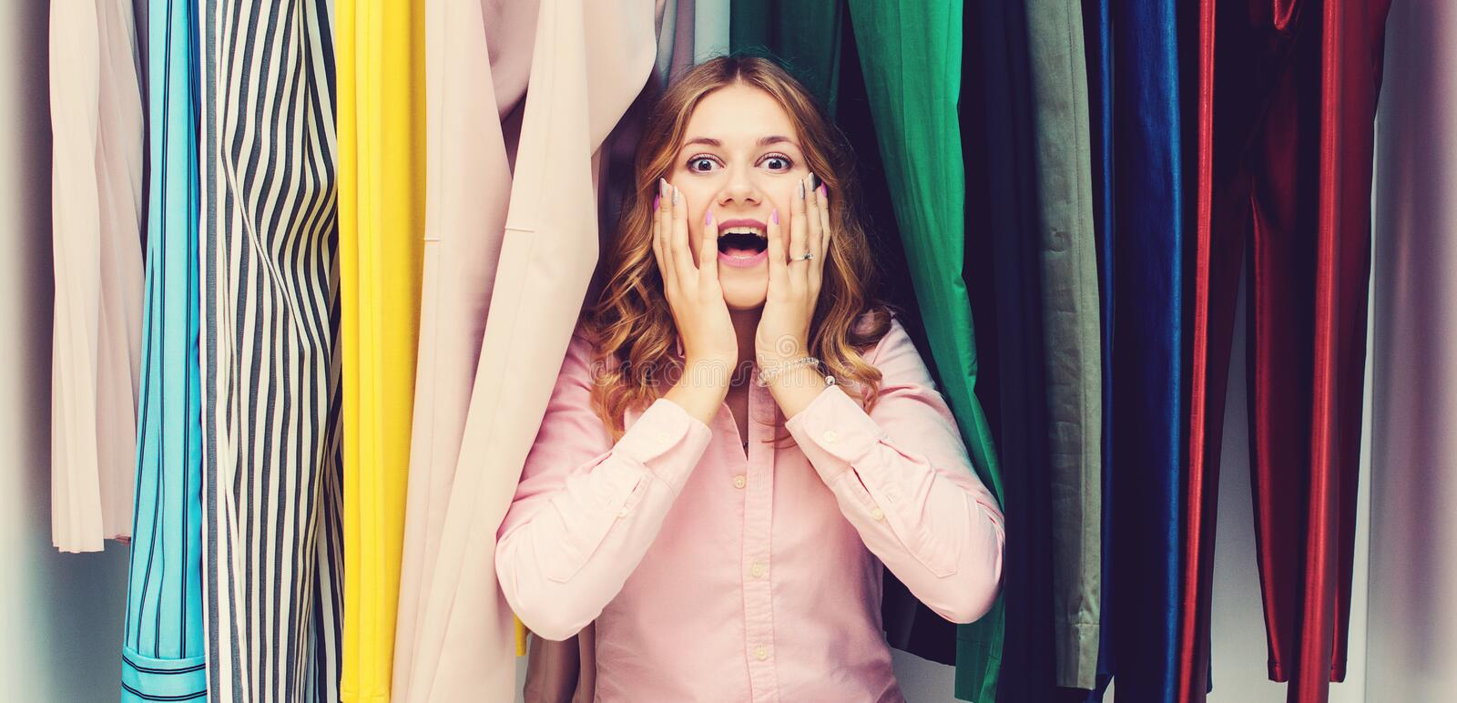 Woman choosing her fashion outfit. Sale, gifts, holidays and people concept. Girl thinking what to wear in front of many choices o. F clothes in organized royalty free stock image