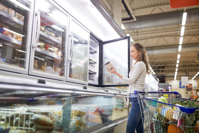Woman choosing ice cream at grocery store freezer. Sale, food, consumerism and people concept - woman with shopping cart choosing ice cream at grocery store stock image