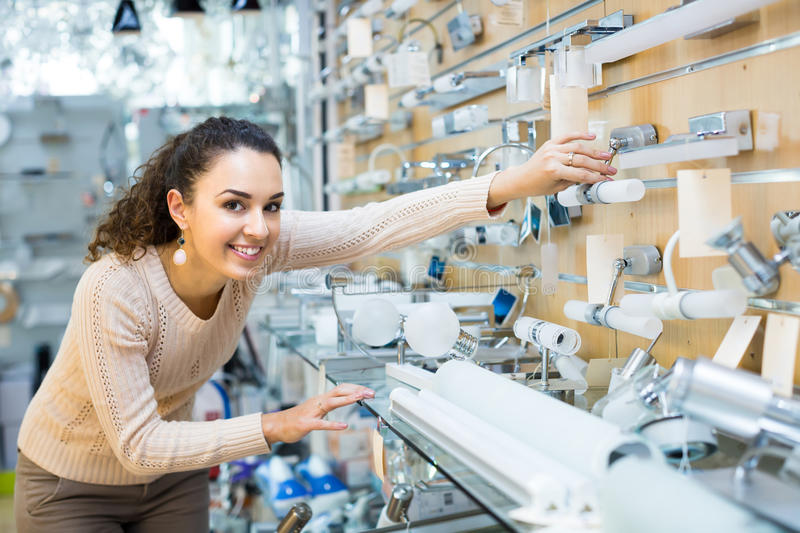 Woman choosing interior lights in mall. Young smiling woman choosing decorative interior lights for home in mall royalty free stock photo