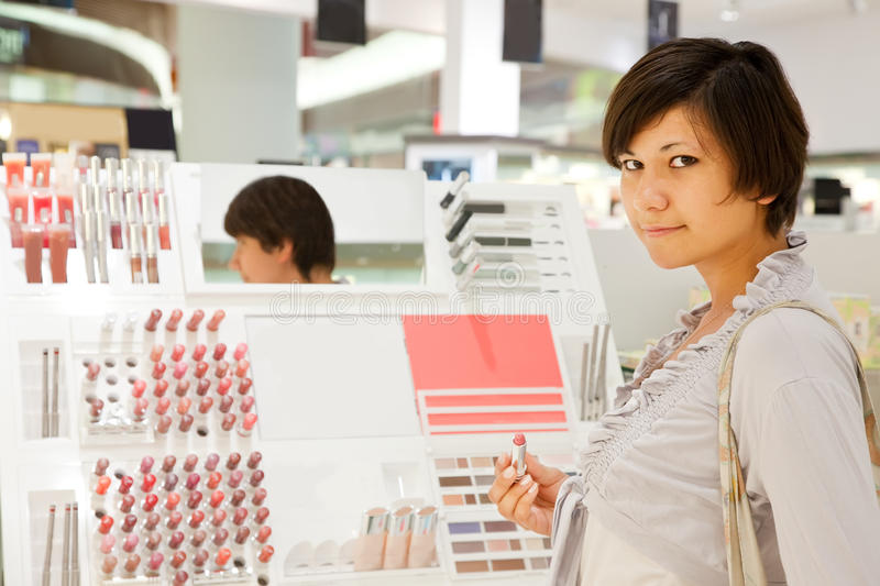 Woman is choosing lipstick royalty free stock images