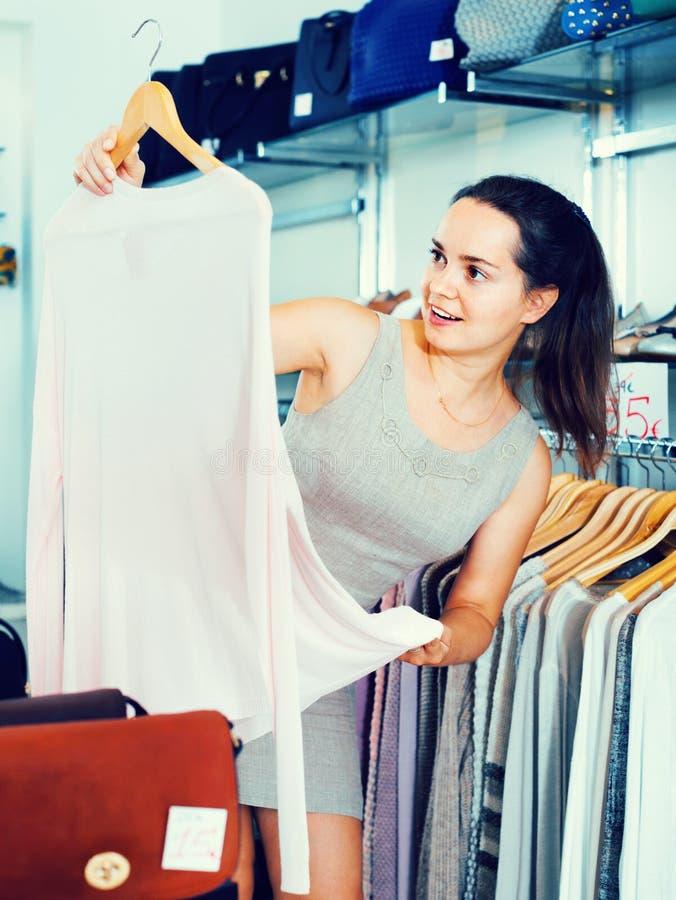 Woman choosing new long sleeve blouse. Happy smiling woman choosing new long sleeve blouse in apparel shop royalty free stock photos