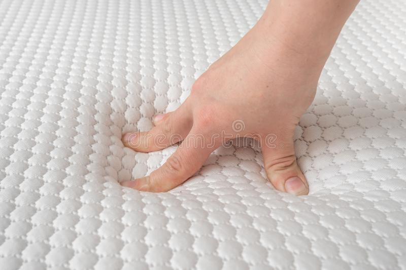 Woman is choosing new mattress for good sleeping. Hand of woman is testing mattress quality royalty free stock image
