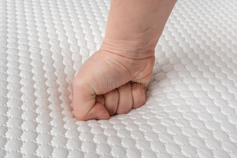 Woman is choosing new mattress for good sleeping. Hand of woman is testing mattress quality stock images