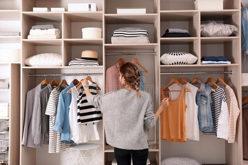 Woman choosing outfit from large wardrobe closet with stylish clothes royalty free stock image