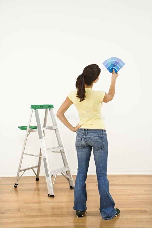 Woman choosing paint color. stock images