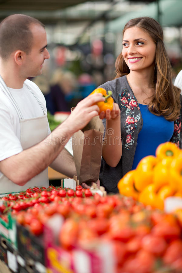 Woman choosing pepper from salesman at street market. Woman choosing yellow pepper from salesman at street market royalty free stock image