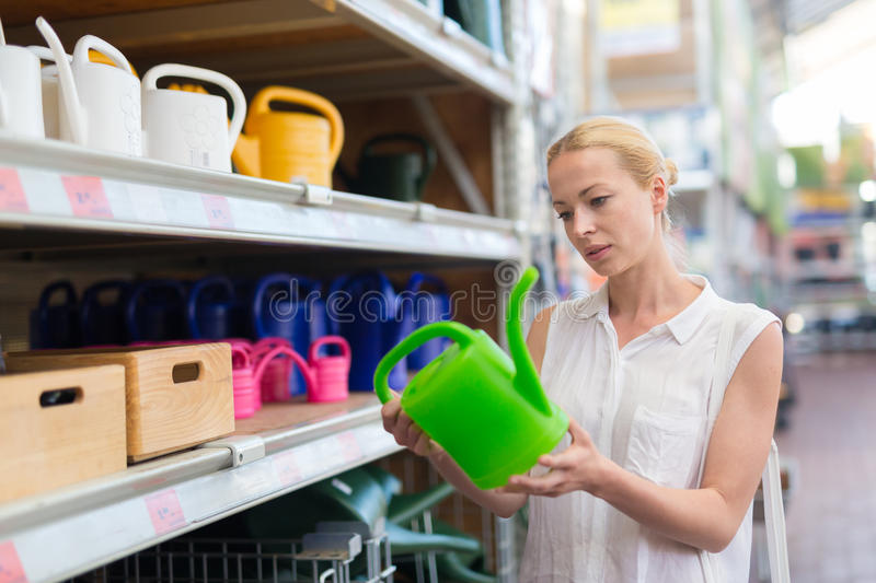 Woman choosing the right item for her apartment in a modern home furnishings store. Beautiful young caucasian woman choosing the right item for her apartment in royalty free stock photography