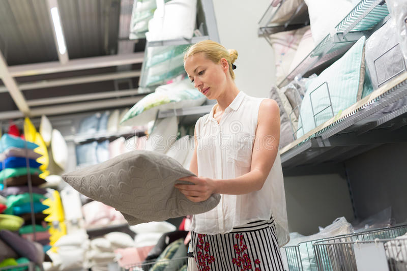 Woman choosing the right item for her apartment in a modern home furnishings store. Pretty, young woman choosing the right item for her apartment in a modern royalty free stock photos