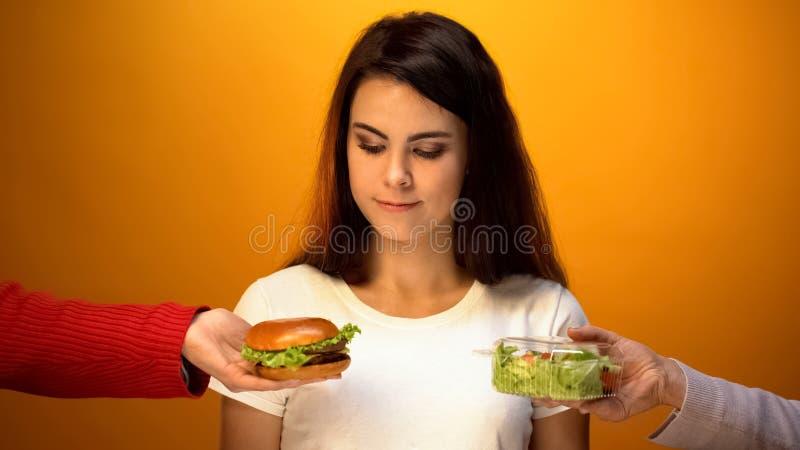 Woman choosing between salad and hamburger, hesitating to make decision, choice royalty free stock images