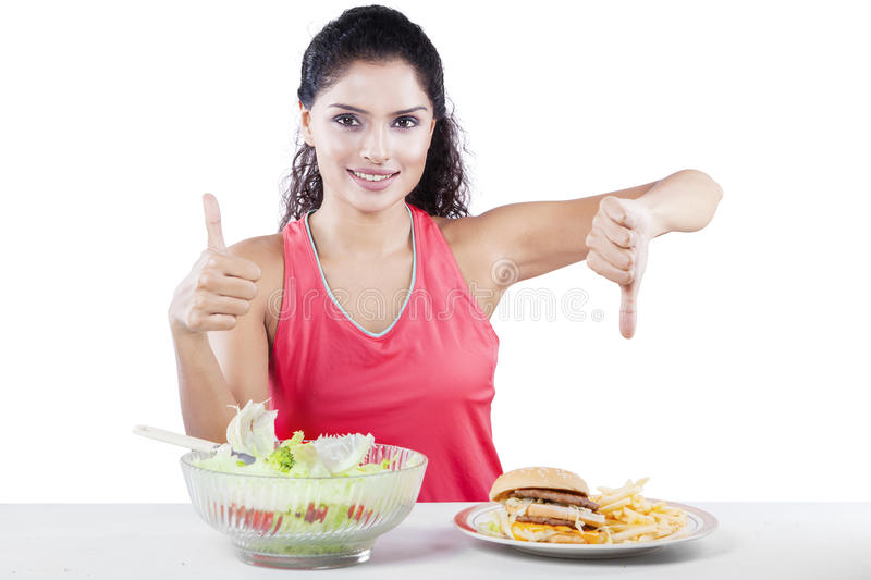 Woman Choosing Between Salad And Junk Food. Dieting concept, beautiful young woman choosing between healthy food and junk food royalty free stock images