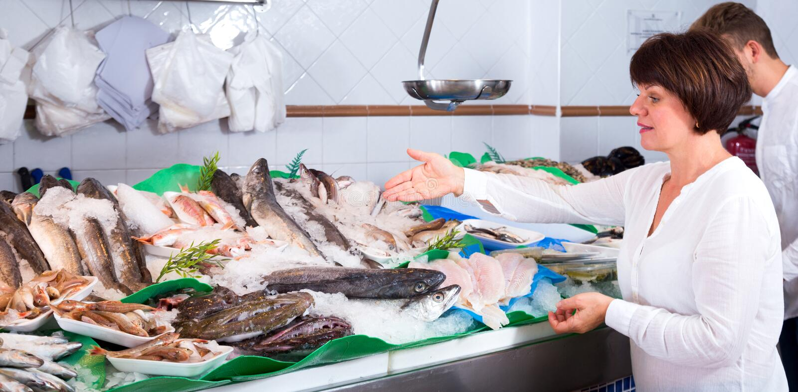 Woman choosing seafood in fish store. Woman client choosing seafood in fish store and smiling royalty free stock photos