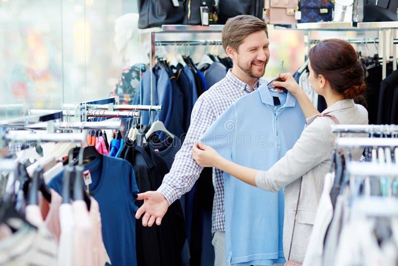 Woman choosing shirt for husband royalty free stock photography