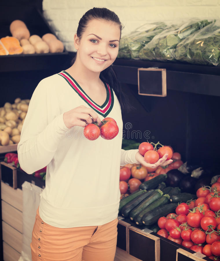 Woman choosing tomatoes in grocery shop stock image