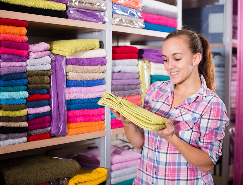 Woman choosing towels. Girl customer deciding on the choice of towels in textile shop stock image