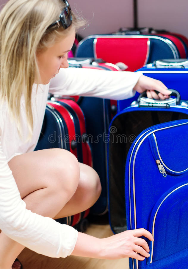 Woman choosing travel suitcase. royalty free stock photography