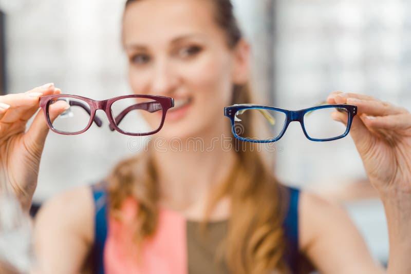 Woman choosing between two models of glasses at optometrist stock images