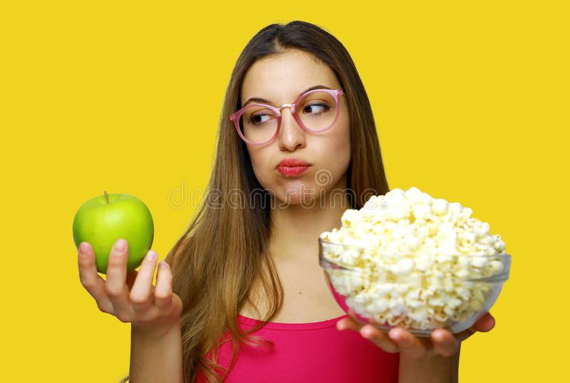 Woman choosing between unhealthy bowl of pop corn and an healthy green apple. Doubt about healthy food, sad to eat an apple stock images