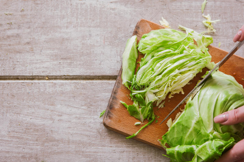 Woman chops cabbage on wooden desk royalty free stock photos