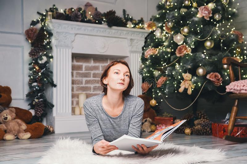 Woman among Christmas decorations reads a book. Beautiful young woman among Christmas decorations reads a book. Family preparing for the New Year holidays royalty free stock images