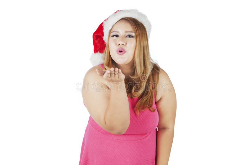 Woman in christmas hat blowing a kiss stock image