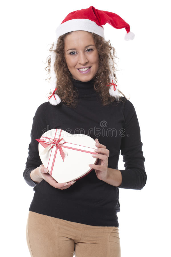Woman with a christmas hat and chocolate box. Beautiful woman with a christmas hat and carrying a chocolate box with the shape of a heart stock photography