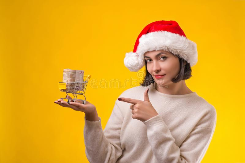 Woman in Christmas hat goes to shopping. Cute girl holding shopping cart with money, isolated on yellow. Woman thinking about royalty free stock photos