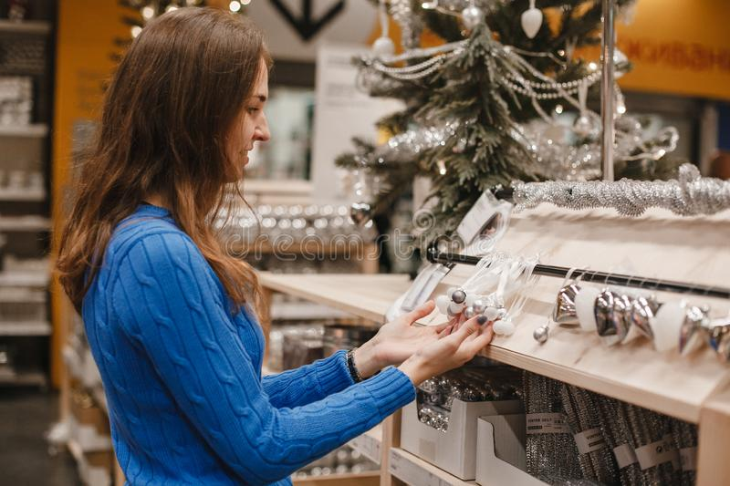 Woman at christmas market choosing decoration and white and silver balls for Christmas tree in New Year shop. Brunette. Smiling girl Shopping. Lifestyle stock images