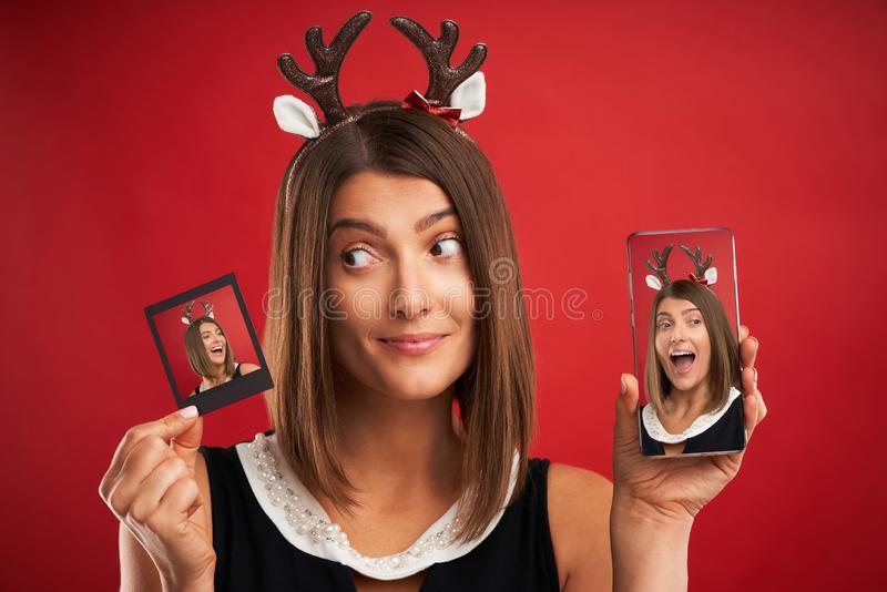 Woman in Christmas mood comparing instant pictures to smartphone camera over red royalty free stock image