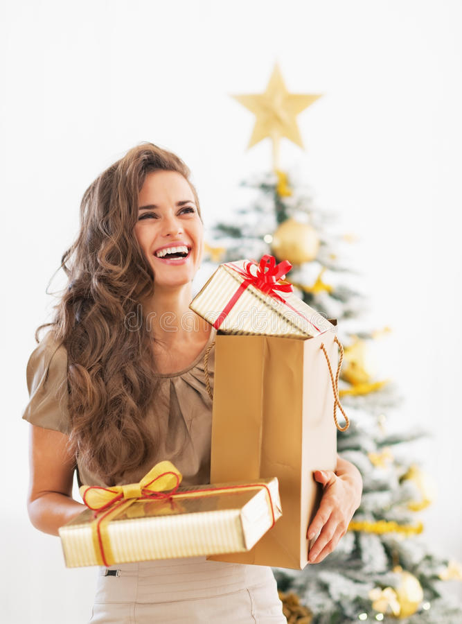 Woman with christmas present boxes in front of christmas tree royalty free stock photography