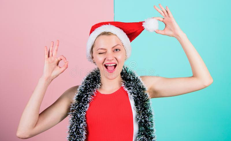 Woman in christmas santa hat play with pompon pink and blue background. Christmas attribute concept. Girl cheerful face. Celebrate christmas. Woman with tinsel stock photo