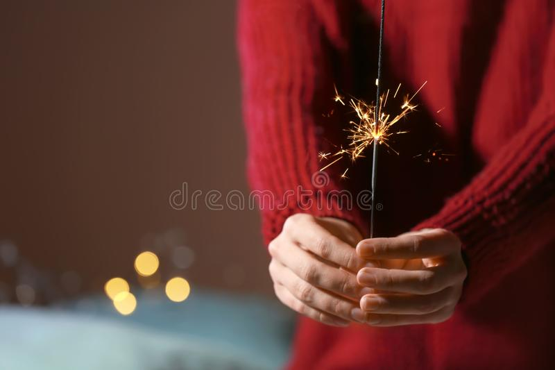 Woman with Christmas sparkler, closeup royalty free stock image
