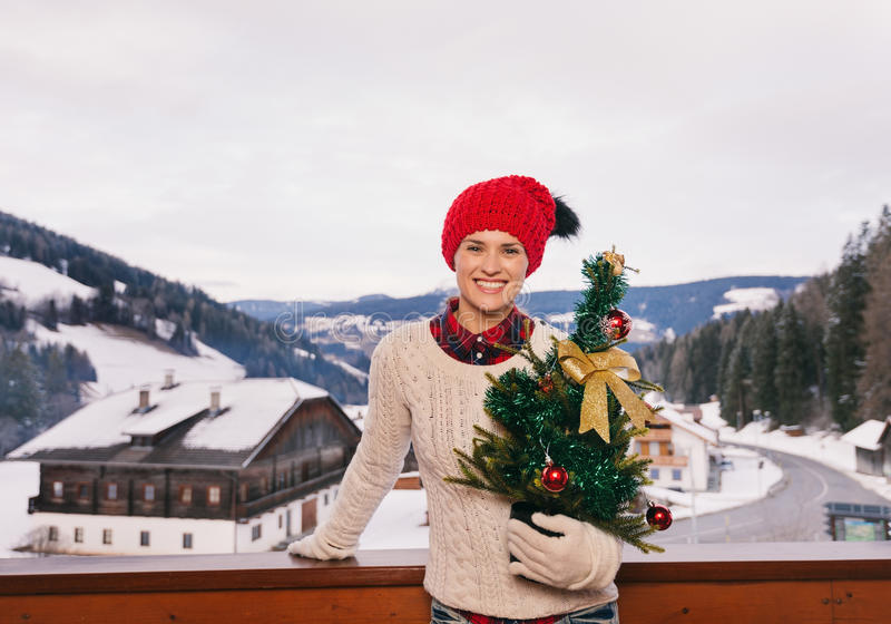 Woman with Christmas tree on balcony overlooking mountains. Mountain cottage hideaway brings calm and warmth into the winter season. Portrait of happy young stock images